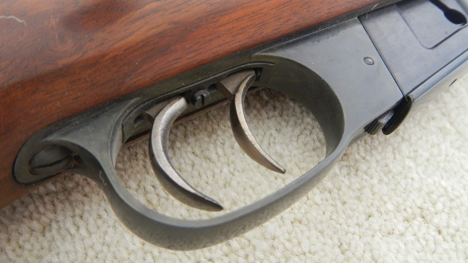 "Double set trigger as commonly found on German and Austrian sporting rifles. The front trigger can be used as a conventional trigger with a normal heavy pull. However, if the rear trigger is pressed first it ""sets"" the front trigger as a light precision trigger. If the trigger needs to be un-set, first apply the safety catch, press and hold the rear trigger, press the front trigger and hold, release the rear trigger, then release the front one. (picture courtesy of The Gourmet Sportsman.)"