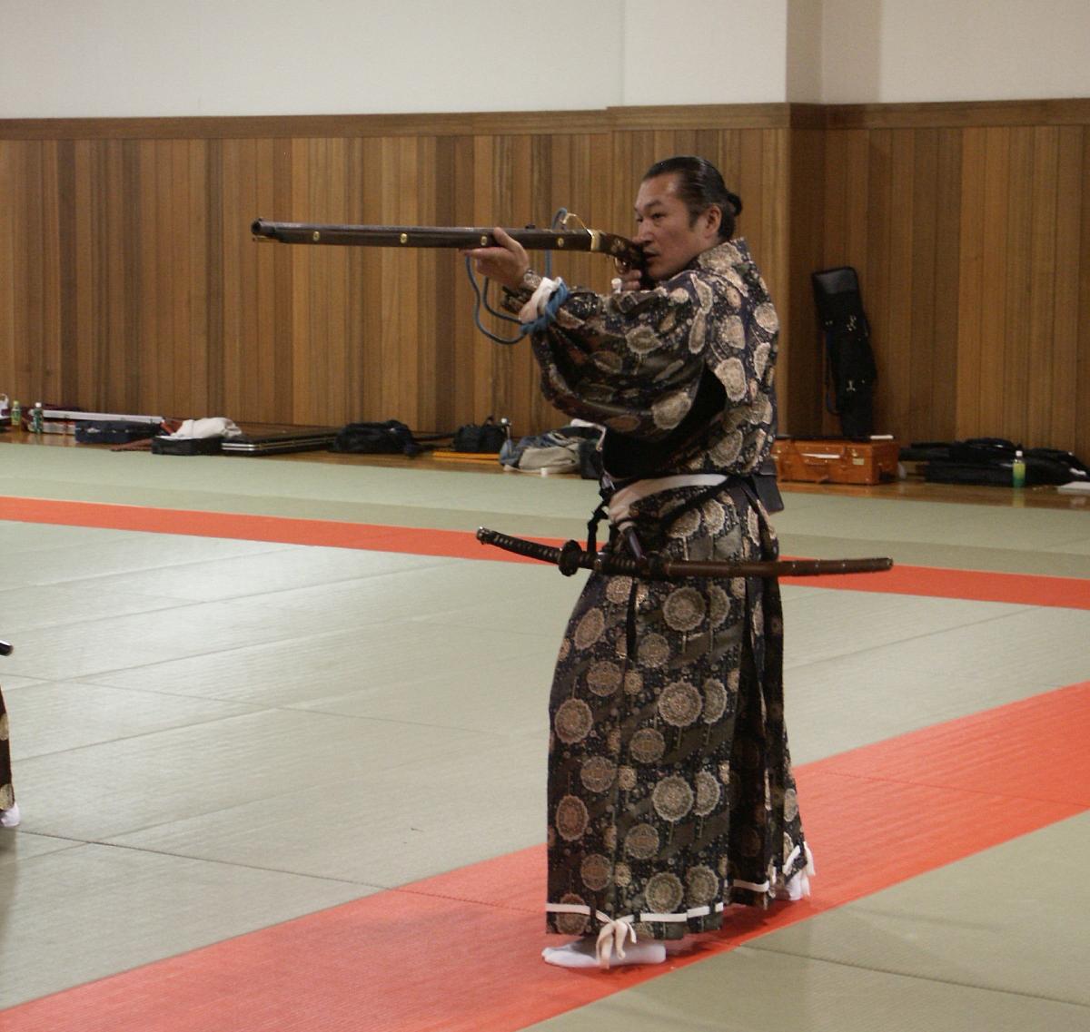 An Edo period tachi sword worn by a member of the Takeda clan as he demonstrates an Edo period matchlock musket.