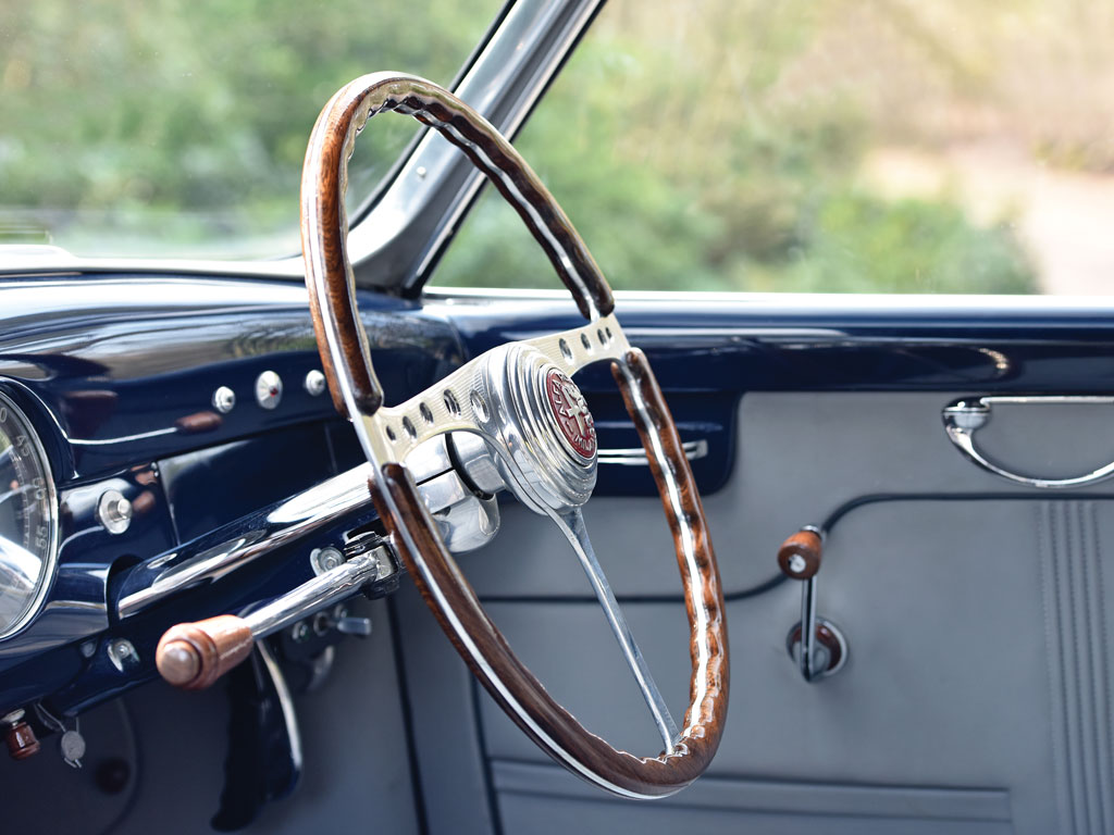 The cockpit is tasteful with a hint of art-deco. The wood on alloy steering wheel is a object of art of itself.