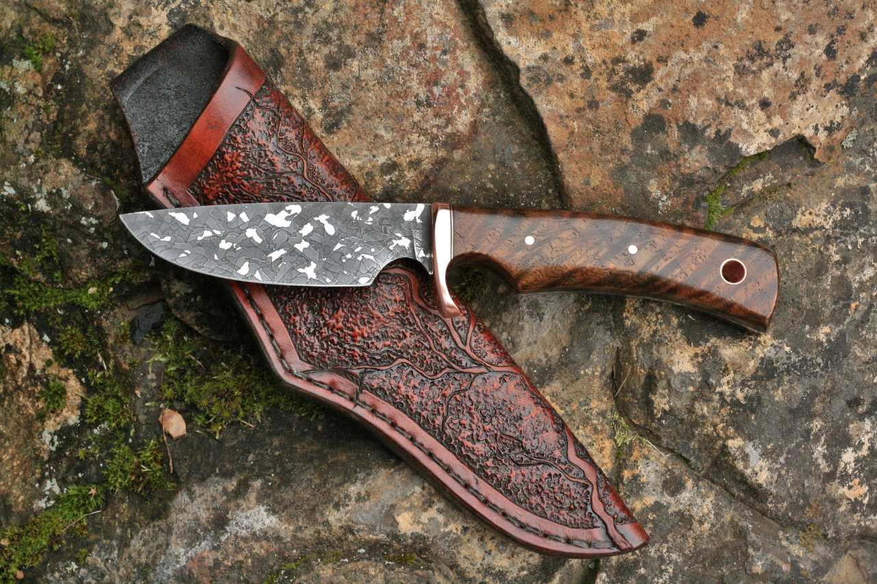 The Large Game Hunter with figured oak grip. Note the finger grooves in the blade and handle which will allow a comfortable and safe grip when holding the knife with the forefinger extended along the spine of the blade for fine work.