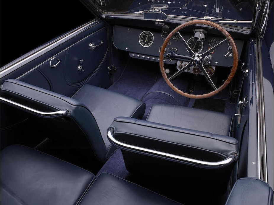 The dark blue interior of the car coordinated delightfully with the black instrumentation, offset by the chrome and wood of the steering wheel.