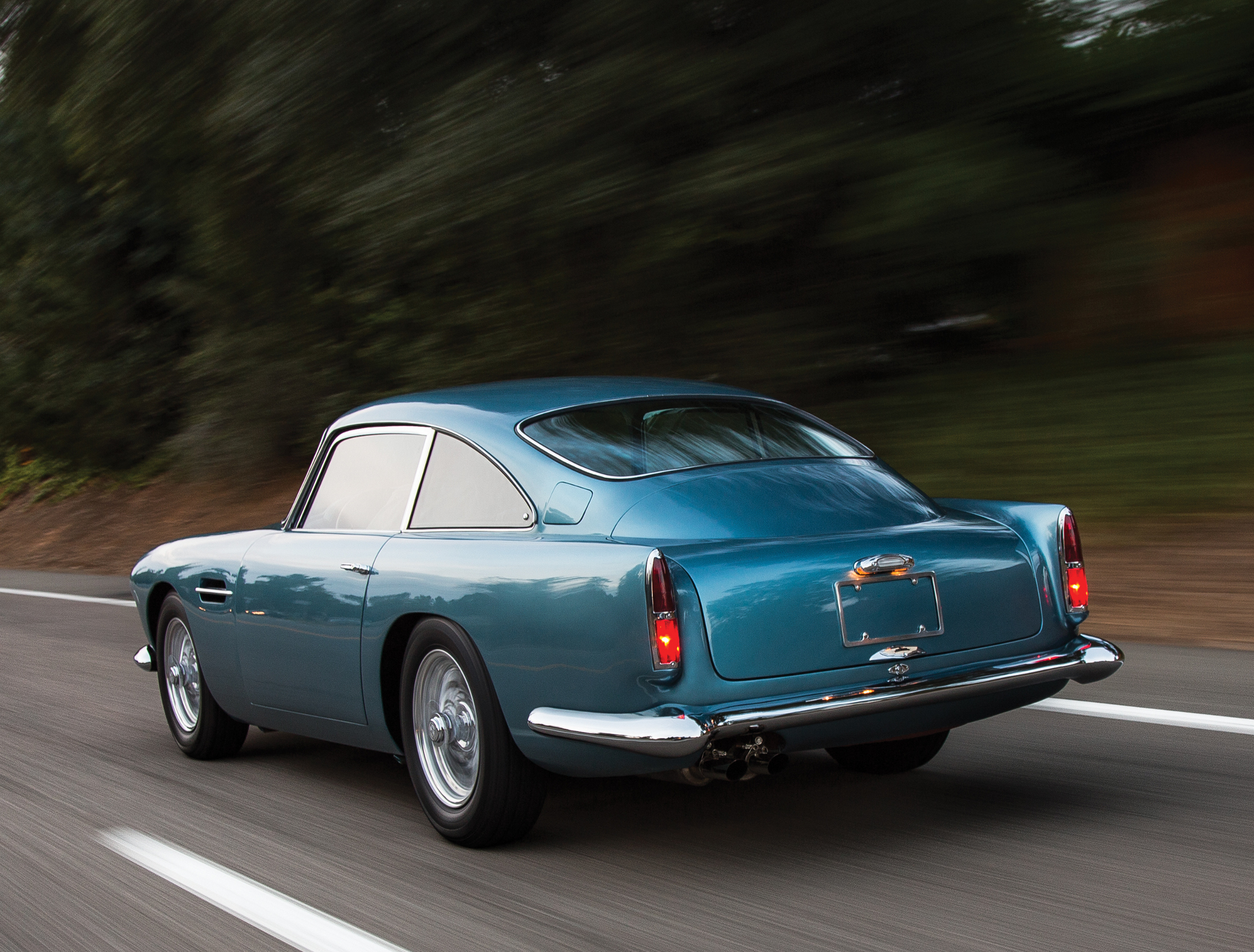 The elegant beauty of the Aston Martin DB4 as commonly admired from a rear quartering angle as one is passed by one.