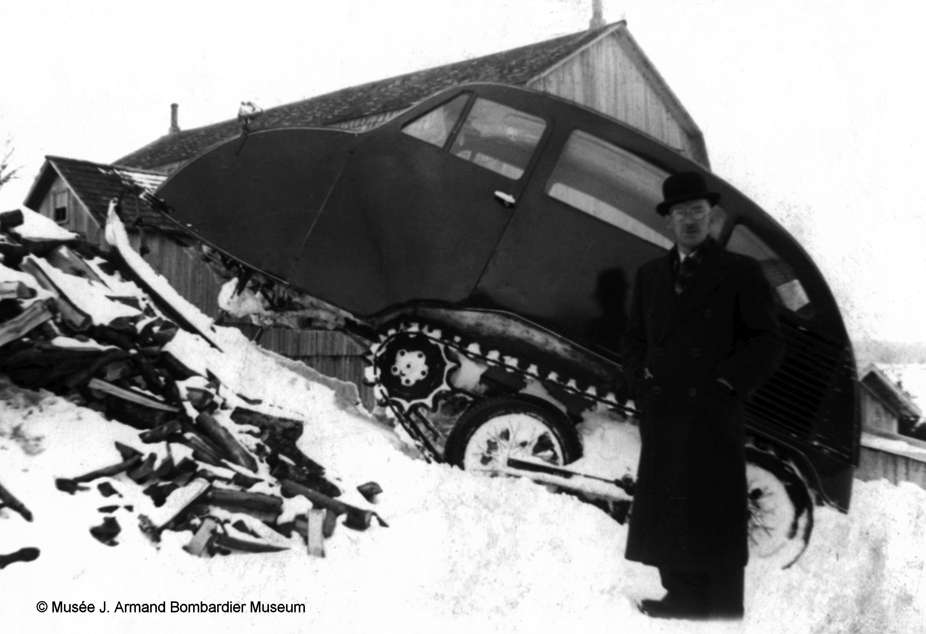"Armande Bombardier with his B7 Snowmobile demonstrating that it can indeed ""climb every mountain and ford every stream"". (Picture courtesy of museebombardier.com)"