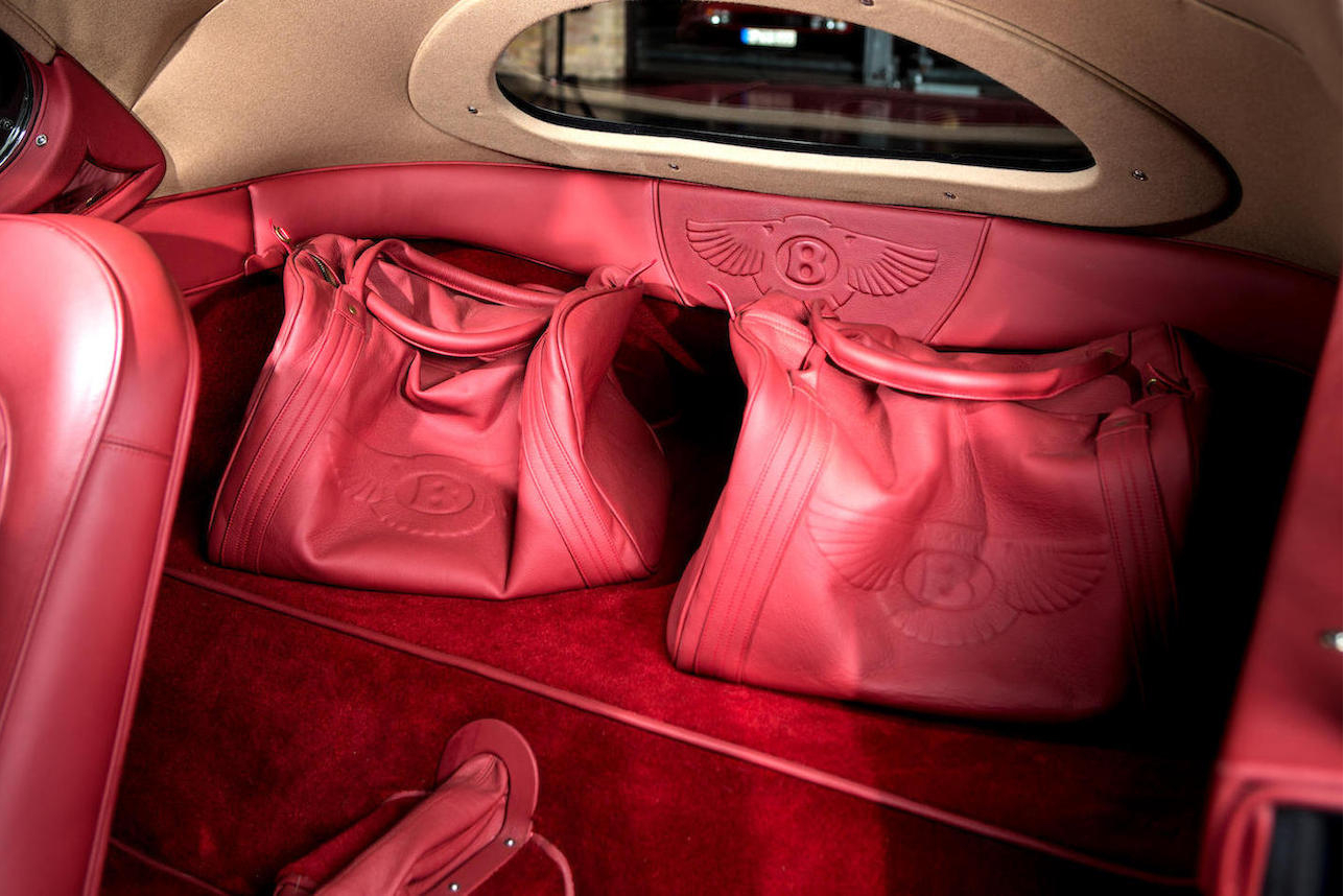 Interior is in tasteful red leather and comes with matching bags.
