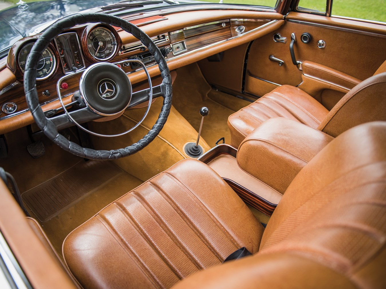 The manual transmission of this 1965 300 SE coupé makes it a luxurious driver's car with opulent mid-tan leather seats and wood veneer dashboard.