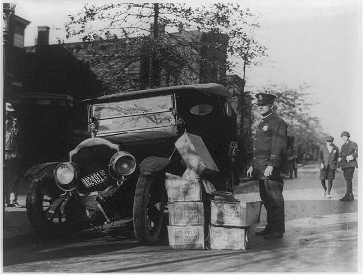 Police Officer and wrecked car with cases of moonshine. (Picture courtesy Wikipedia).