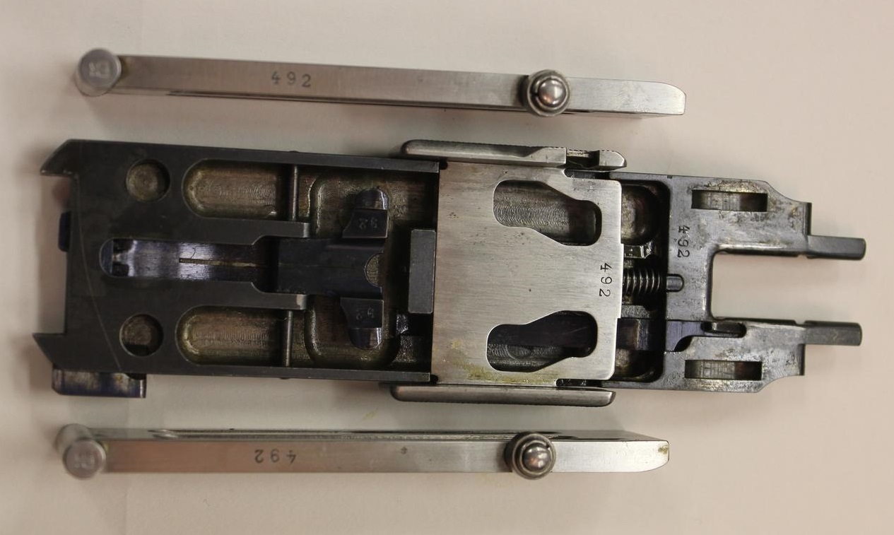 This picture shows the plate with its angled slots with the flaps that would normally engage in those slots removed and laid by the side of the breech block for this photograph.