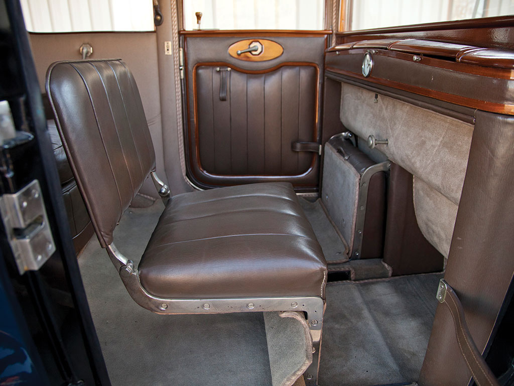 The passenger compartment of this landaulet has folding occasional seats in addition to the main rear passenger seat.